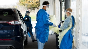 Health care workers put on personal protective equipment before testing at a drive-thru COVID-19 assessment centre at the Etobicoke General Hospital in Toronto on Tuesday, April 7, 2020. THE CANADIAN PRESS/Nathan Denette