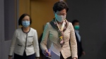 Hong Kong Chief Executive Carrie Lam, right, arrives at a press conference in Hong Kong, Tuesday, June 2, 2020. (AP Photo/Vincent Yu)