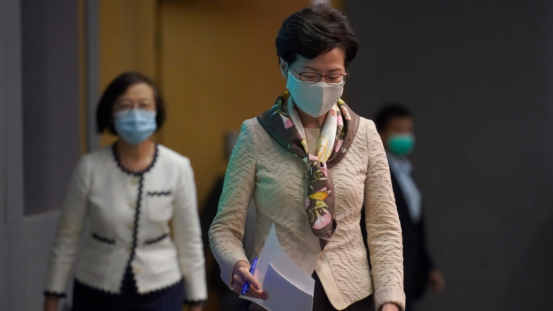 Hong Kong Chief Executive Carrie Lam, right, arrives at a press conference in Hong Kong, Tuesday, June 2, 2020. (AP Photo/Vincent Yu)