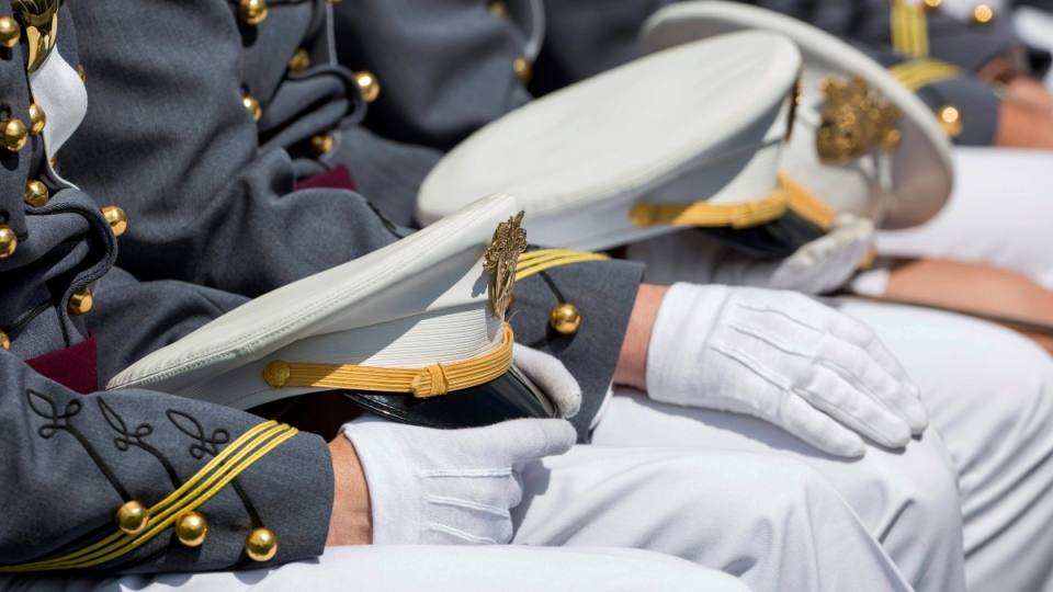 West Point cadets hold their caps on their laps