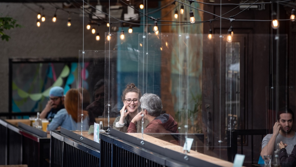 Patrons sit between plexiglass barriers on the patio of a restaurant and bar in Vancouver, on Sunday, May 31, 2020. THE CANADIAN PRESS/Darryl Dyck