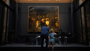 A limited amount of visitors admire Rembrandt's Night Watch, rear, at the reopened Rijksmuseum in Amsterdam, Netherlands, Monday, June 1, 2020. (AP Photo/Peter Dejong)