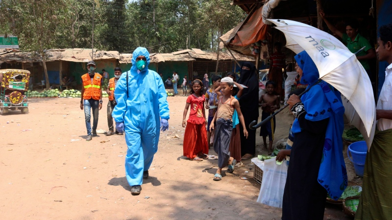 FILE - In this April 15, 2020, file photo, a health worker from an aid organization walks wearing a hazmat suit at the Kutupalong Rohingya refugee camp in Cox's Bazar, Bangladesh. (AP Photo/Shafiqur Rahman, File)