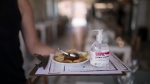 A waitress carries menus and hand sanitizer at a seafood restaurant in Marseille, southern France, Tuesday, June 2, 2020. (AP Photo/Daniel Cole)