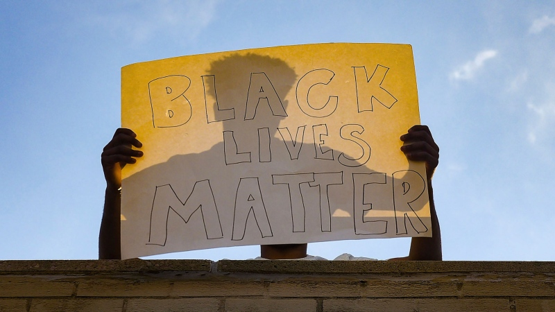 A protestor holds a 'Black Lives Matter' sign on top of a building on Sunday, May 31, on Main Avenue in Sioux Falls, S.D. (Erin Bormett/The Argus Leader via AP)