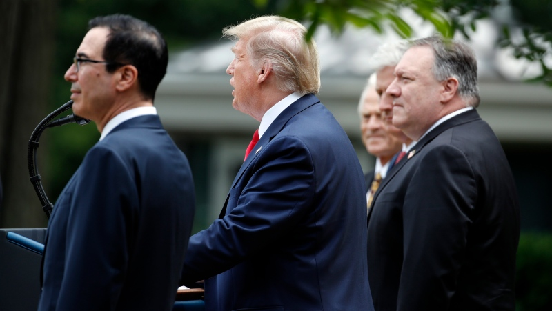 U.S. President Donald Trump speaks in the Rose Garden of the White House, Friday, May 29, 2020, in Washington, as from left, Treasury Secretary Steven Mnuchin, White House trade adviser Peter Navarro, left, White House national security adviser Robert O'Brien, and Secretary of State Mike Pompeo, listen. (AP Photo/Alex Brandon)