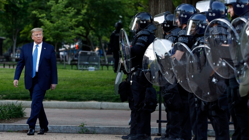 U.S. President Donald Trump walks past police in Lafayette Park after he visited outside St. John's Church across from the White House Monday, June 1, 2020, in Washington. Part of the church was set on fire during protests on Sunday night. (AP Photo/Patrick Semansky)