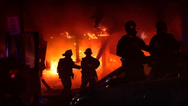 St. Louis firefighters are protected by police officers as they put out a fire at at looted 7-Eleven convenience store in St. Louis, on June 1, 2020. (Robert Cohen / St. Louis Post-Dispatch via AP)
