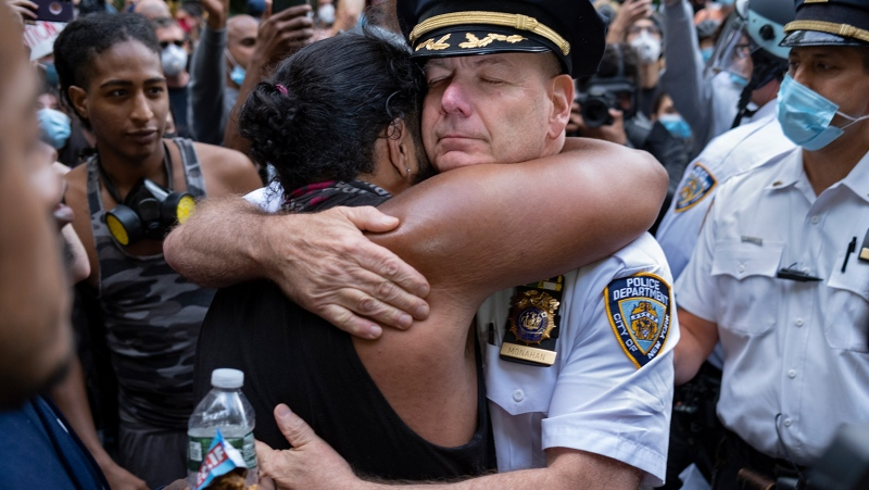 Chief of Department of the New York City Police, Terence Monahan, hugs an activist. (Craig Ruttle/AP)