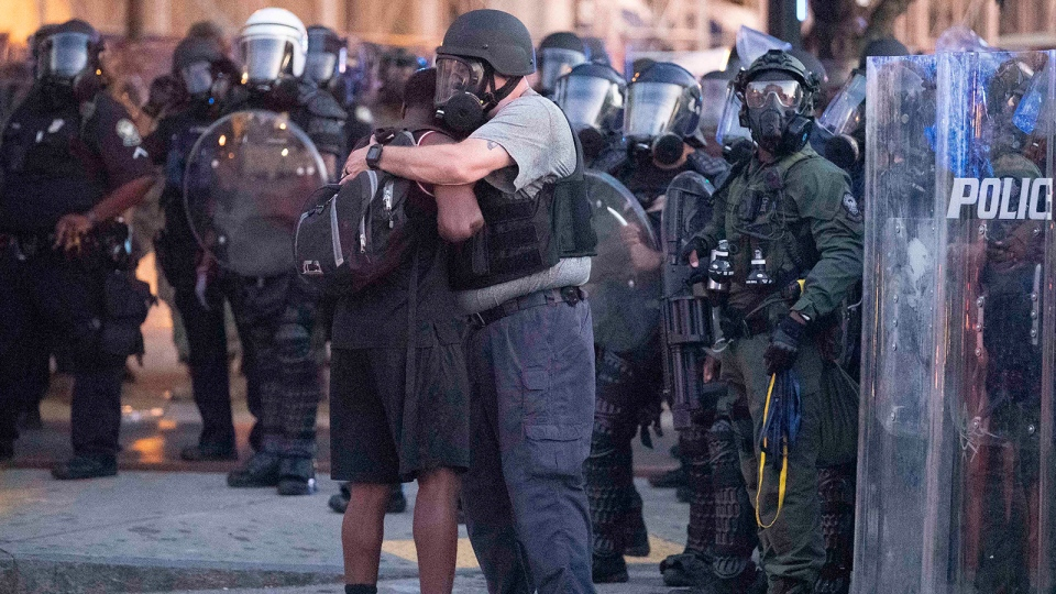 An officer clad in a helmet and mask hugs a protester. (John Bazemore/AP)