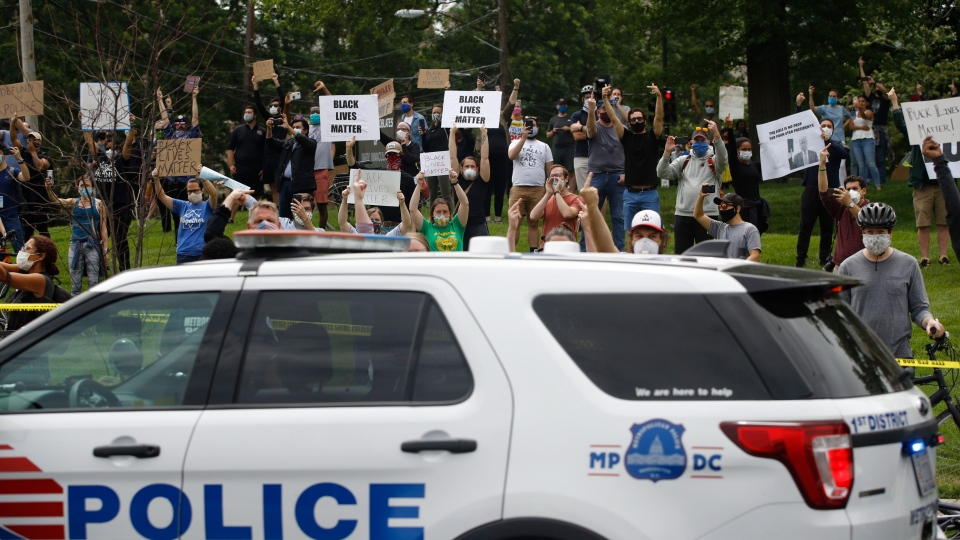 People gather to protest as the motorcade for U.S. President Donald Trump passes by en route to Saint John Paul II National Shrine, Tuesday, June 2, 2020, in Washington. (AP Photo/Patrick Semansky)