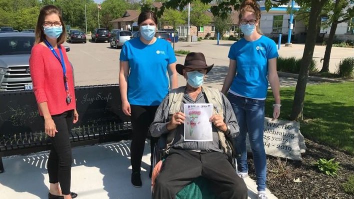 "Ivan Thompson, a senior from Dutton, Ontario holds a ""letter of positivity"" picture created by a local students in West Lorne Ontario on Tuesday, June 2 2020. He is joined by members of the local community health centre and Meals on Wheels Program. (Sean Irvine/CTV London)"