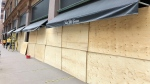 The windows to Saks Fifth Avenue on Queen Street West are shown boarded up on Tuesday morning. (Newstalk 1010)