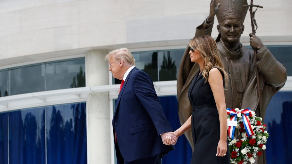 U.S. President Donald Trump holds first lady Melania Trump's hand as they visit Saint John Paul II National Shrine, Tuesday, June 2, 2020, in Washington. (AP Photo/Patrick Semansky)