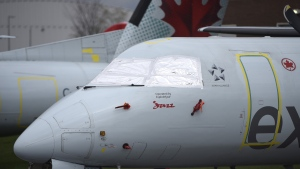 The windshield of an Air Canada Express aircraft is covered as it sits parked at the Ottawa International Airport in Ottawa, in the midst of the COVID-19 pandemic, on Saturday, May 16, 2020. Air Canada says it has raised $1.59 billion in share and debt offerings to refill its coffers as cash drains out during the COVID-19 pandemic. (Justin Tang/THE CANADIAN PRESS)