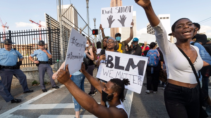 Activists demonstrate Monday, June 1, 2020, in Atlanta, while police guard a ramp onto the interstate, as they march from downtown to North Avenue protesting the recent killing of George Floyd. (John Amis/Atlanta Journal-Constitution via AP)