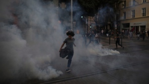 A protester kicks in a tear gas canister during a demonstration Tuesday, June 2, 2020 in Marseille, southern France. (AP Photo/Daniel Cole)