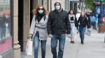 People with face masks and without face masks walk along Sainte-Catherine street in Montreal, Sunday, May 31, 2020, as the COVID-19 pandemic continues in Canada and around the world. THE CANADIAN PRESS/Graham Hughes