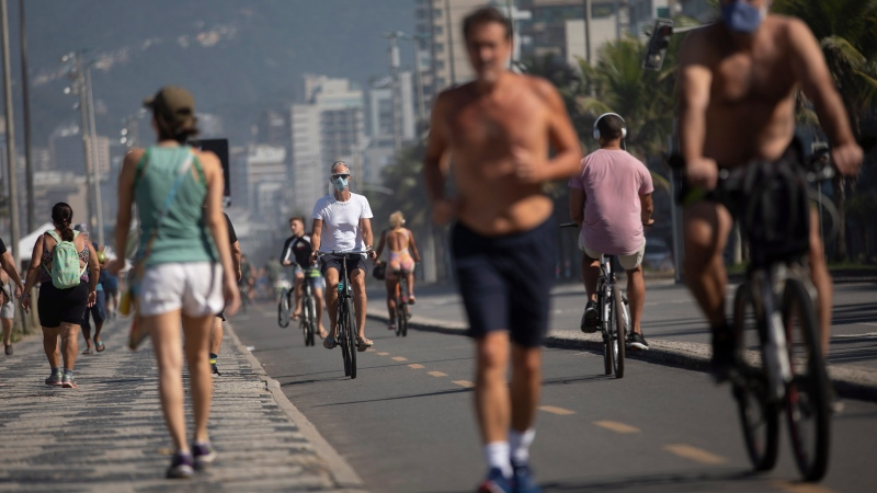 People exercise along the seashore at Ipanema beach in Rio de Janeiro, Brazil, Tuesday, June 2, 2020, amid the new coronavirus pandemic. (AP Photo/Silvia Izquierdo)