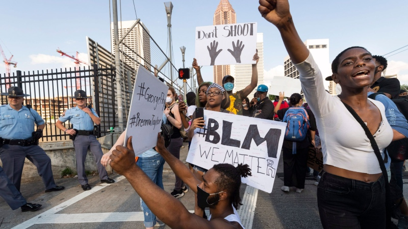 Activists demonstrate Monday, June 1, 2020, in Atlanta, while police guard a ramp onto the interstate, as they march from downtown to North Avenue protesting the recent killing of George Floyd. The killing of Floyd by police in Minnesota has sparked worldwide protests and rioting nationwide. (John Amis/Atlanta Journal-Constitution via AP)