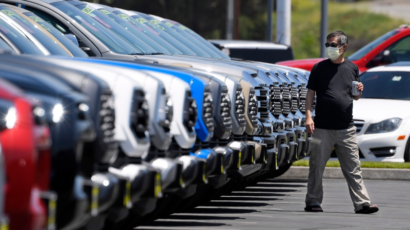 A customer looks at trucks at Longo Toyota during the coronavirus outbreak, Friday, May 8, 2020, in El Monte, Calif. (AP Photo/Mark J. Terrill)