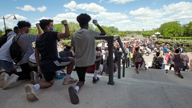 Hundreds of people take a knee while participating in a Black Lives Matter demonstration in front of Saskatchewan's Legislative Building in Regina, Sask., Tuesday June 2, 2020. THE CANADIAN PRESS/Mark Taylor.