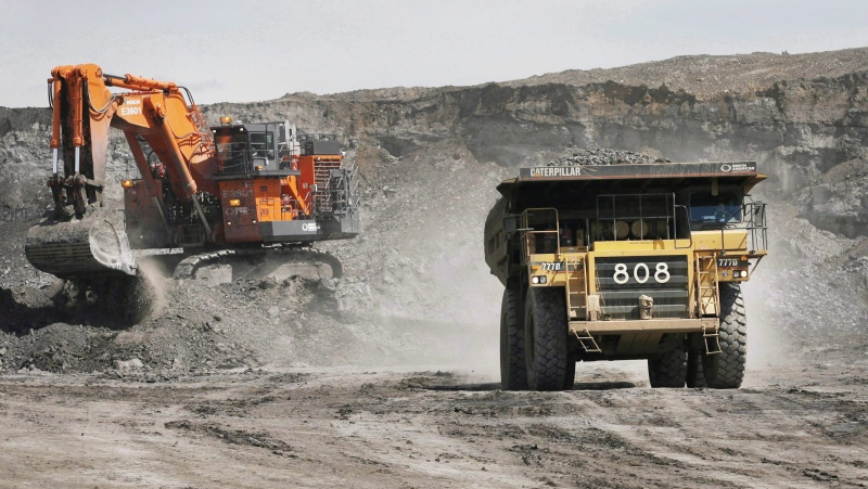In this file photo, a haul truck carrying a full load drives away from a mining shovel at the Shell Albian Sands oilsands mine near Fort McMurray, Alta., Wednesday, July 9, 2008. A new report is accusing the global mining industry of prioritizing profit at the expense of workers and local communities during the pandemic. THE CANADIAN PRESS/Jeff McIntosh