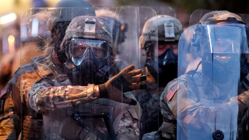 Georgia National Guard troops prepare to enforce a 9:00 pm curfew as demonstrators chant, Tuesday, June 2, 2020, in Atlanta. Protests continued following the death of George Floyd, who died after being restrained by Minneapolis police officers on May 25. (AP / John Bazemore)