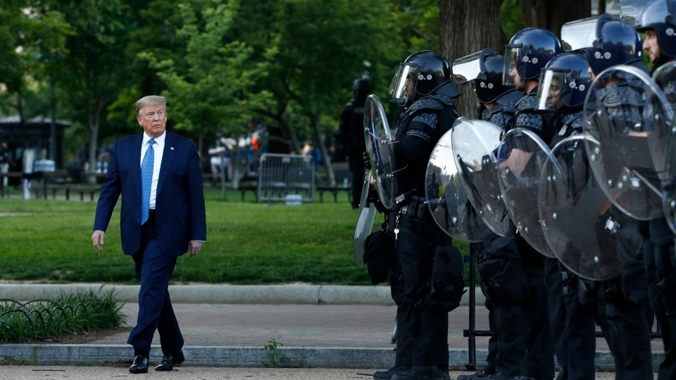 In this Monday, June 1, 2020, file photo, President Donald Trump walks past police in Lafayette Park after visiting outside St. John's Church across from the White House in Washington. (AP Photo/Patrick Semansky, File)