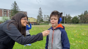 Tracey Abeysundera is helping her son Rayne Edwards blow a dandelion. June 2, 2020. Ottawa, ON. (Tyler Fleming / CTV News Ottawa)