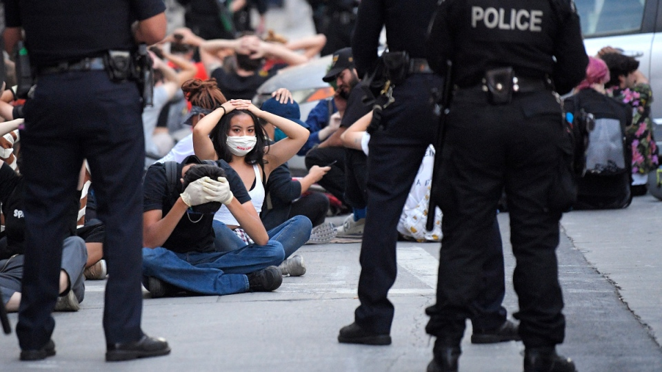 Demonstrators put their hands on their heads before being taken into custody in Los Angeles on June 2, 2020. (Mark J. Terrill / AP)
