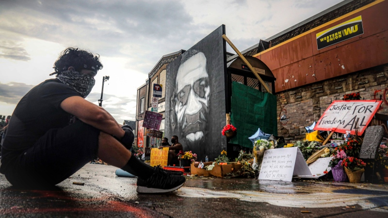 After a new mural, center, of George Floyd is added to a growing memorial of tributes, Trevor Rodriquez sits alone at the spot where Floyd died while in police custody, Tuesday June 2, 2020, in Minneapolis, Minn.(AP Photo/Bebeto Matthews)