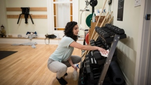 Zeena Dotiwalla cleans dumbbells at Yogaspace in Toronto on Wednesday, March 11, 2020. Many exercise buffs are feeling torn between the desire stay active and concerns about contracting the novel coronavirus at the gym.Several Canadian fitness centres have been assuring clients that they're beefing up their hygiene protocols in response to the COVID-19 outbreak. (THE CANADIAN PRESS / Tijana Martin)