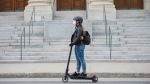 A woman wears a face mask as she rides a scooter by the Museum of Fine Arts in Montreal, Sunday, May 31, 2020, as the COVID-19 pandemic continues in Canada and around the world. THE CANADIAN PRESS/Graham Hughes