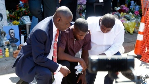 Quincy Mason, center, the son of George Floyd, family attorney Ben Crump, left, kneel, Wednesday, June 3, 2020 as they visited the site of a memorial in Minneapolis where Floyd was arrested on May 25 and died while in police custody. Video shared online by a bystander showed a white officer kneeling on his neck during his arrest as he pleaded that he couldn't breathe. (AP Photo/Jim Mone)f
