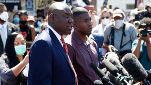 Quincy Mason, right, a son of George Floyd, listens Wednesday, June 3, 2020 as family attorney Ben Crump, left, addresses a news conference as they and some Floyd family members visited a memorial in Minneapolis where Floyd was arrested on May 25 and died while in police custody. Video shared online by a bystander showed a white officer kneeling on his neck during his arrest as he pleaded that he couldn't breathe. (AP Photo/Jim Mone)