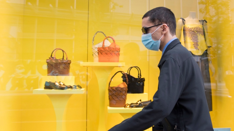 A pedestrian wears a protective face mask as they walk past a re-opened shop in downtown Vancouver, Tuesday, June 2, 2020. Various businesses and restaurants are opening in the province as a part of the phase 2 reopening plan during the COVID-19 pandemic. THE CANADIAN PRESS/Jonathan Hayward