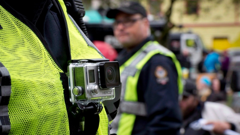 A member of the Vancouver Police Department wears a chest mounted camera as he oversees the take down of a tent city in downtown Vancouver on Oct. 16, 2014. (THE CANADIAN PRESS / Jonathan Hayward)