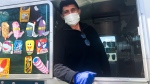 Mister Softee ice cream truck driver, Mutlu Gani, pauses for a photo while waiting for customers Saturday, April 11, 2020 in the Brooklyn borough of New York. (AP Photo/Jake Seiner)