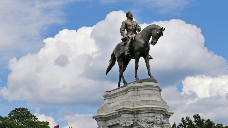 This Tuesday June 27, 2017 file photo shows the statue of Confederate General Robert E. Lee that stands in the middle of a traffic circle on Monument Avenue in Richmond, Va. (AP Photo/Steve Helber, file)