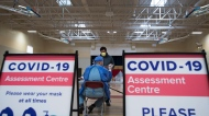 A man gets instructions for being tested for COVID-19 from a health care worker at a pop-up testing centre in Scarborough, Ont., on Friday, May 29, 2020. THE CANADIAN PRESS/Nathan Denette