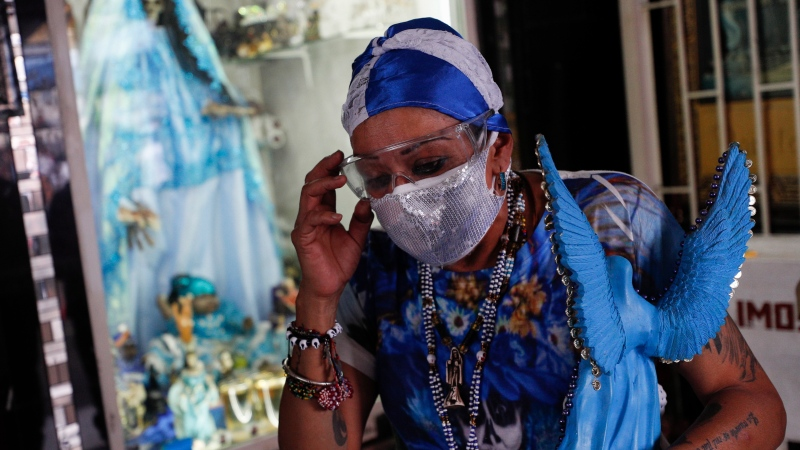 """A woman adjusts her protective goggles as she leaves after visiting an altar to the """"Santa Muerte,"""" or Death Saint, in Mexico City's Tepito neighborhood, Monday, June 1, 2020. (AP Photo/Rebecca Blackwell)"""