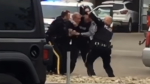 Three Kelowna RCMP officers attempt to take a man into custody in a parking lot on May 30, 2020. (Castanet.net)