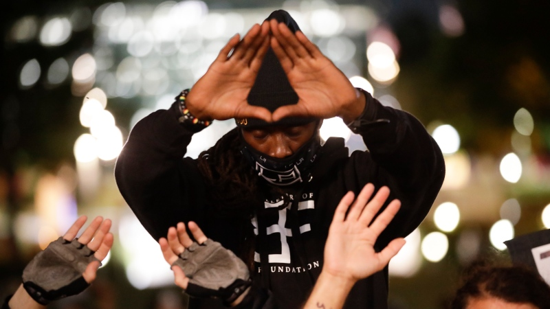 A demonstrator makes gesture shortly before being arrested for a curfew violation Wednesday, June 3, 2020 in downtown Los Angeles during a protest over the death of George Floyd who died May 25 after he was restrained by Minneapolis police. (AP Photo/Marcio Jose Sanchez)