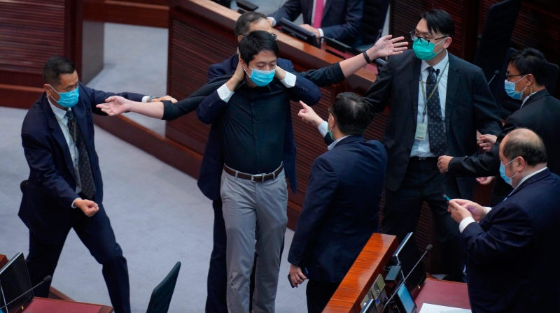 Hui Chi-fung, pro-democracy lawmaker, is warned by security at the main chamber of the Legislative Council in Hong Kong, Thursday, June 4, 2020. Hong Kong's legislature approved a contentious bill Thursday that makes it illegal to insult the Chinese national anthem. The legislation was approved after pro-democracy opposition lawmakers tried to disrupt the vote. (AP Photo/Vincent Yu)