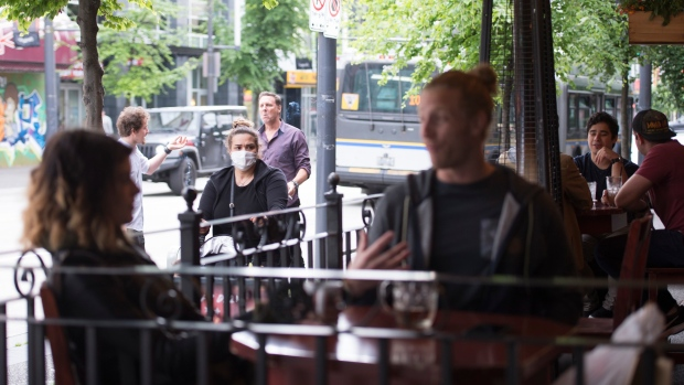 A woman wears a protective face mask as she walks past a opened restaurant patio on Granville Street in Vancouver, Wednesday, May 20, 2020. British Columbia has entered into phase 2 of the provinces re-start plan allowing some business to reopen. THE CANADIAN PRESS/Jonathan Hayward