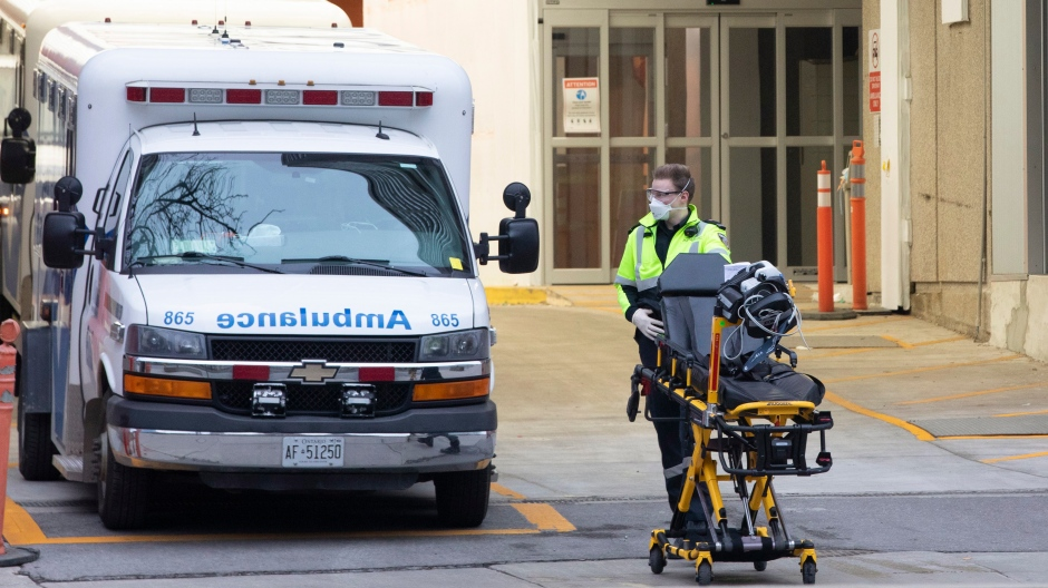 A paramedic pushes a gurney outside Toronto's Mount Sinai Hospital on Saturday, March 28, 2020. (Chris Young/The Canadian Press)
