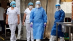Health Ministry nurses wearing protective gear arrive to test for COVID-19 from employees of Barrio Obrero General Hospital, in Asuncion, Paraguay, Thursday, May 21, 2020. (AP Photo/Jorge Saenz)
