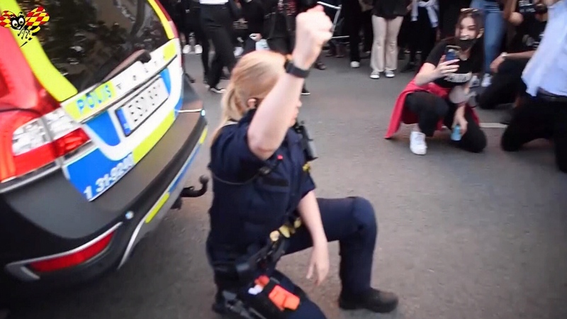 Officer kneels with protesters in Sweden
