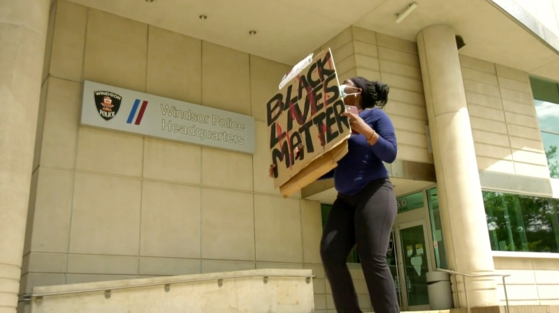As part of a silent protest, a lone demonstrator holds a 'Black Lives Matter' sign outside of the Windsor Police Service headquarters in downtown Windsor on June 4, 2020. (Rich Garton / CTV Windsor)